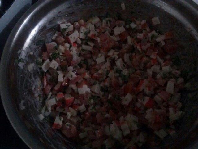 Ensalada de palitos de cangrejo, tomate, cebolla y perejil.