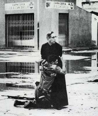 """1963 - Hector Rondon's Award of The Republic for this photo titled """"Aid form the Father"""", in which a wounded soldier is held by a priest in the insurrection in Venezuela last year."""