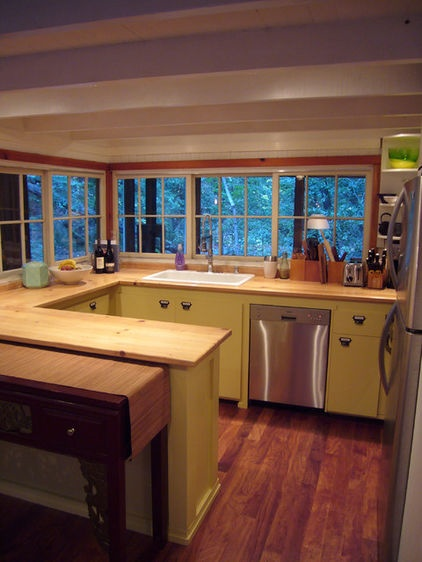 he simple kitchen is for the most part original to the home. The homeowners updated the appliances, painted the cabinetry and added new hardware but kept the original wood countertops. The stovetop is just around the corner from the refrigerator.