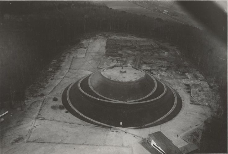 Mogiła Mogił /Kopiec Piłsudskiego na Sowińcu. Jeszcze w trakcie budowy - widać sterty ziemi, kamienie, rampy. Budowa kopca rozpoczęła się 6 sierpnia 1934 roku - w 20. rocznicę wymarszu z Krakowa Pierwszej Kompanii Kadrowej. Sypanie stożka zakończono 9 lipca 1937 r., jednak prace wykończeniowe trwały jeszcze do 1939 r. Na plac budowy przyjeżdżali ludzie z całej Polski - zarówno delegacje, jak i osoby prywatne.  Zdjęcie ze zbiorów Muzeum Lotnictwa Polskiego w Krakowie.