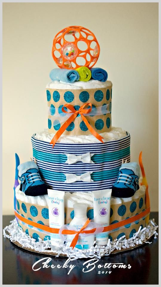 Lovely three tiered diaper cake for a little boy.  This gift is created with: 52 Pampers Swaddlers (size 2), 1 receiving blanket (middle tier), two baby spoons, 3 baby Live Clean products, 1 pair baby booties, 3 baby washcloths and 1 O-Ball toy.