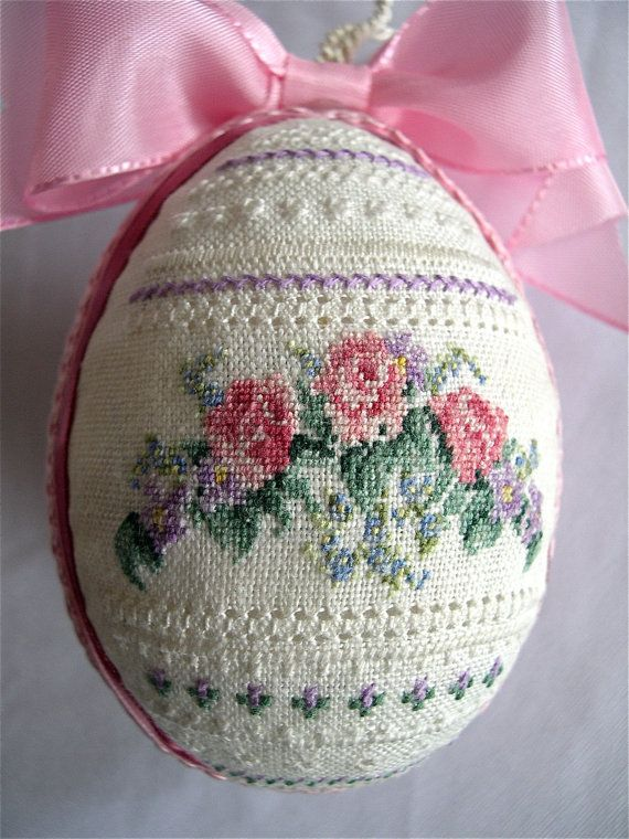 Row upon row of intricate needlecraft play on this light-as-a-feather egg. A spray of pink roses, violets and for-get-me-nots are handstitched on natural 100% Belgian linen at a scale of 32 stitches per inch. Satin and grosgrain ribbons and cording encircle, and a pink satin bow and silky cream hanging cord perch at the top. The back is unstitched linen.    This delicate egg measures four inches high and three inches across. Although just created, it truly has the look and feel of an…