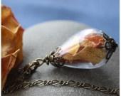 Pétales de roses séchés et perles de verres soufflées à la main. Un peu de printemps à porter sur soi.  Dimensions (perles et attaches inclues): 45 cm Dimension des perles : 2.7cm poids : 4g  Matériaux utilisés : Breloques et attaches en Bronze sans plomb et sans nickel, Chaînes lien mère-fils : 4x3.5mm Perles de Verres soufflée à la main : transparente. Pétales de rose séchés : jaune orangé