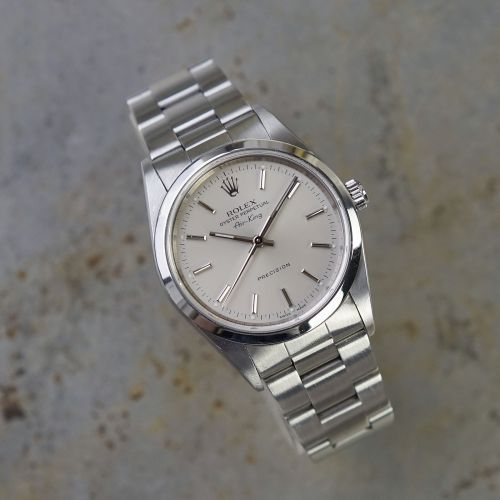 """A lovely, historically-rich, original Rolex Air King 14000M series watch manufactured in 2000. One of the longest running watch series in the Rolex line, it has a distinct aeronautic pedigree in Rolex's production of professional activity watches. With its automatic movement calibre 3130, 34mm steel case, silver baton dial, sapphire crystal. The Rolex 78350/557 bracelet will fit a 7.5"""" wrist. A little history The Rolex Air King model dates back to the … Read More →"""