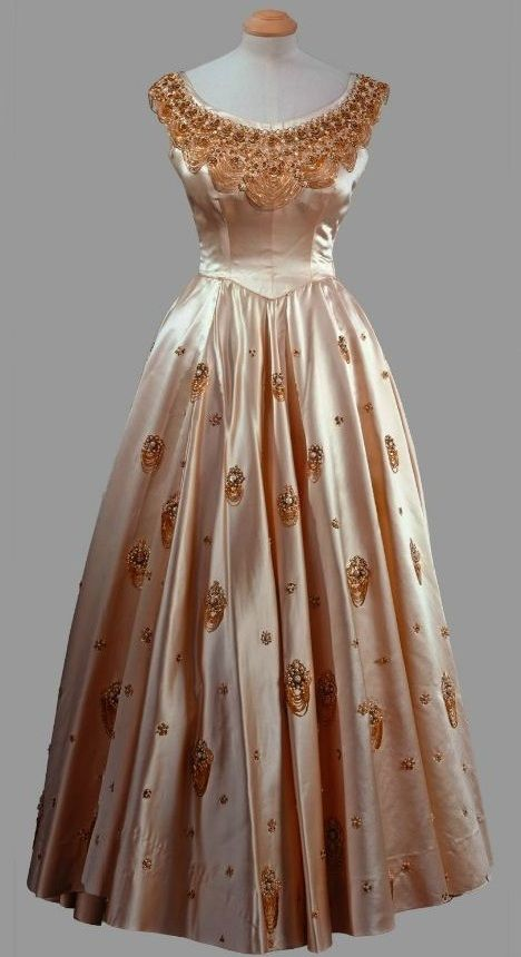 Evening Dress, Norman Hartnell: 1956, silk, heavily-looped metallic embroidery. Worn [by HRH Queen Elizabeth II] for a visit to the House of Representatives in Lagos during the Royal Tour of Nigeria, February 1956.