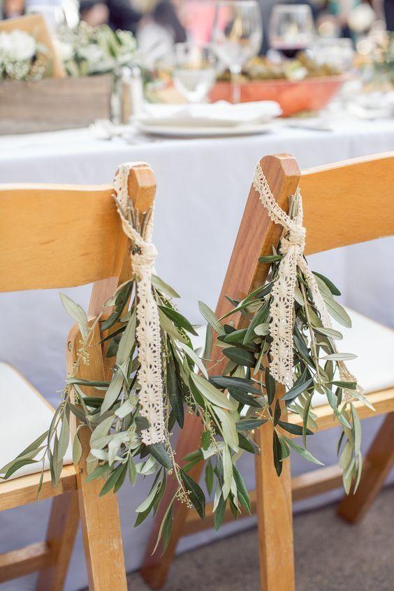 decorazione sedie matrimonio con nastri di pizzo e foglie d'ulivo