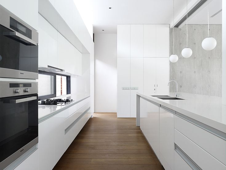 :: KITCHENS :: - modern sleek designed kitchen. Sharp lines and white with black, stainless steel and deep brown wood accents.