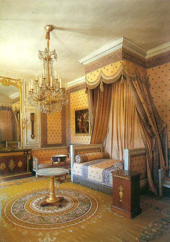 The Empire Aubusson Rug in the Emperor's bedroom has a circular central medallion on a gold background with large open areas. The motifs are in the neoclassical style of Percier and Fontaine favored by Napoleon. The gold of the Aubusson rug and blue silk fabric are on opposite ends of the color wheel. Image courtesy Wikipedia Commons.