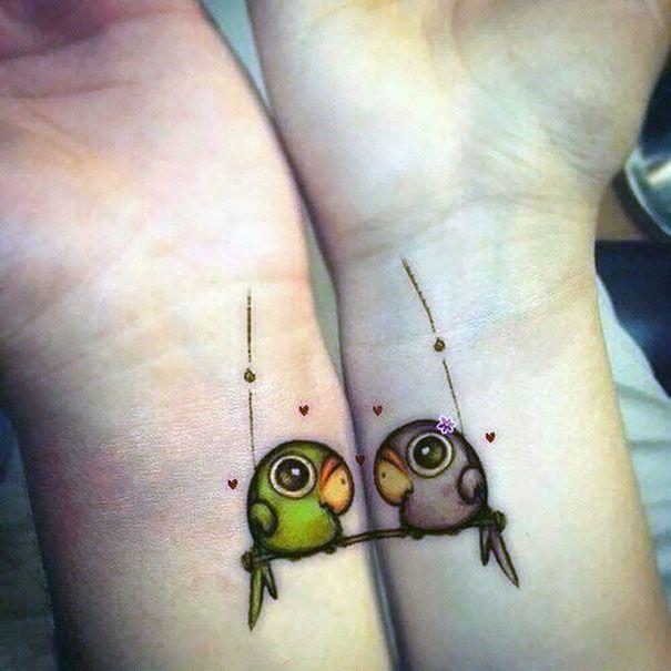 Muñecas de una pareja con tatuajes en forma de pericos