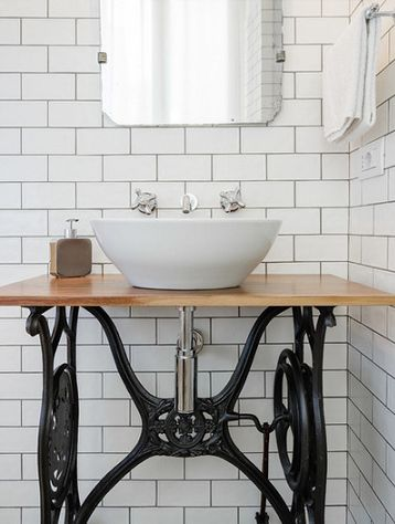 In the other bathroom is a sink on a stand made from an antique Singer sewing machine table's cast iron base; the wooden top ties in with shelving found elsewhere in the home. Patterned cement tiles on the floor contrast the white subway wall tiles that climb up to the ceiling.