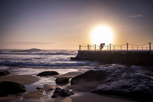 A swimmer taking their morning dive at Curl Curl Swimming Pool in NSW Australia