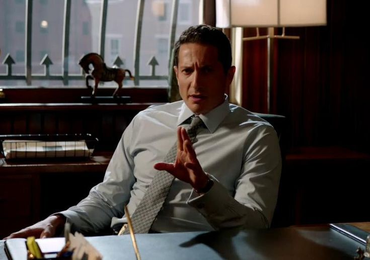 Jean Renard is sitting after his desk with a grey shirt and polka dot tie