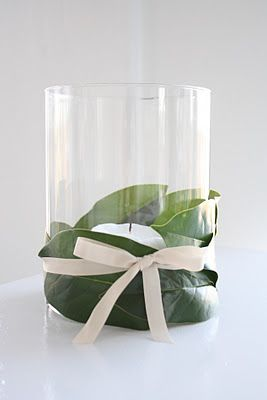 Another simple idea for using magnolia leaves is to use ribbon to tie a few of them around a cylindrical vase containing a pillar candle, as...