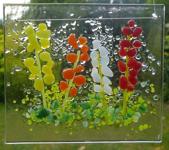Gesmolten glas zomer bloem suncatcher. Deze mooie suncatcher heeft een zeer tactiele ontwerpen met behulp van ondoorzichtige geel, oranje, wit en rood gekleurde frit voor bloemen op helder glas gesmolten. Groene frit en poeder is gebruikt voor de grond. Dit ontwerp van de bloem eruit mooi opknoping in een venster of op een muur. Grootte ongeveer 89 x 100 mm (3 1/2 x 4)
