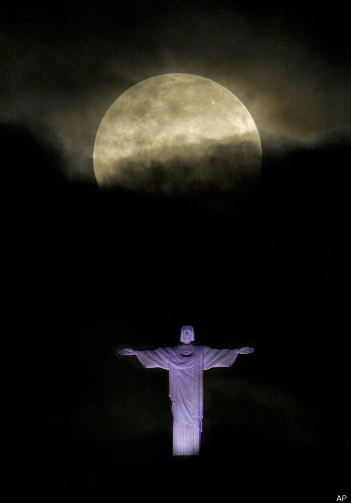 """A """"supermoon"""" is seen above the Christ the Redeemer statue in Rio de Janeiro, Sunday, May 6, 2012. A supermoon is the coincidence of a full moon (or a new moon) with the closest approach the moon makes to the Earth. (AP Photo/Victor R. Caivano)"""
