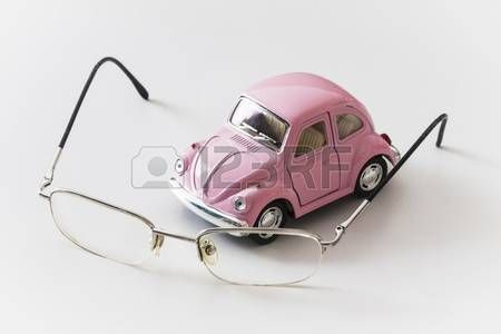 Pink toy car is on a white desk near the eyeglasses
