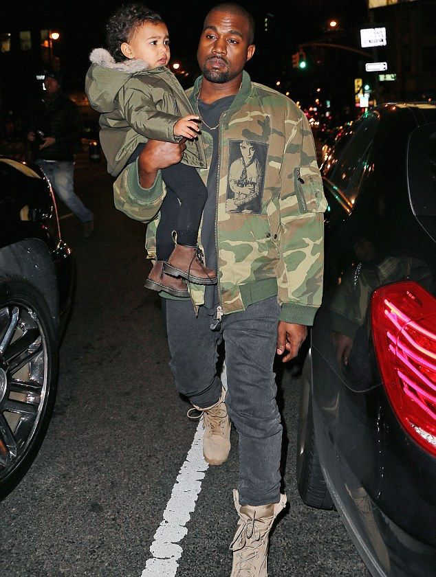 Kany-West-wears-Raf-Simons-Camo-Flight-Jacket-and-Army-Boots-Shoes-while-carrying-North-West