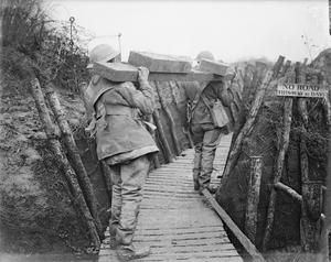 WWI, March 1917; British troops with timber for a trench support through a communication trench at Ploegsteert. ©IWM (Q 5092)