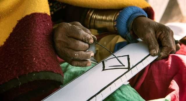 Photo of Esther Mahlangu painting with a chicken feather