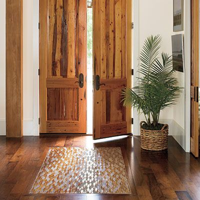"""A custom glass tile """"area rug"""" inset in the foyer sets an artful tone for the house. The warm colors and dark grout make a glamorous statement in the simple space."""