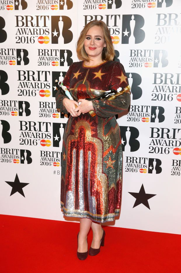 Adele toting her two statuettes in the winners room at the 2016 Brit Awards on…