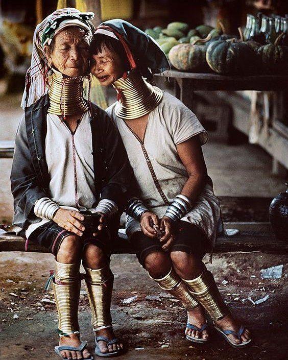 """""""O coração de uma mulher é tão maravilhoso como uma gota de água sobre uma flor de lótus"""" Próverbio Tailandês  Em casas de palha nos vilarejos da região montanhosa ao norte da Tailândia vivem as mulheres girafas. Pertencem à tribo dos Karen Padaung.  Para esse grupo o centro da alma é o pescoço responsável por proteger os habitantes e a identidade da tribo.  Os Padaung também acreditam que a beleza da mulher é proporcional ao comprimento de seu pescoço. E para que ele cresça cada vez mais…"""