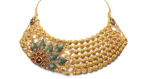 Seven rows of oval gold beads form the base of this elegant necklace. The highlight of this necklace is a seven petaled flower and seven leaves that are brought to life in exquisite red and green enamel work.