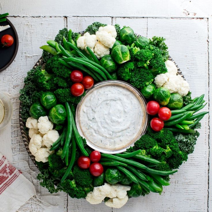 Take your veggies and dip to the next level with this colorful crudité wreath. This vegetable appetizer is a stunner with white cauliflower, red tomatoes and green broccoli, green beans, snap peas, kale and Brussels sprouts. It's also a delicious way to start your celebration with veggies (which there are rarely enough of at parties and holidays). The homemade ranch dip, which uses nonfat Greek yogurt in place of sour cream, takes just a few minutes to make, or you can use a healthy store...