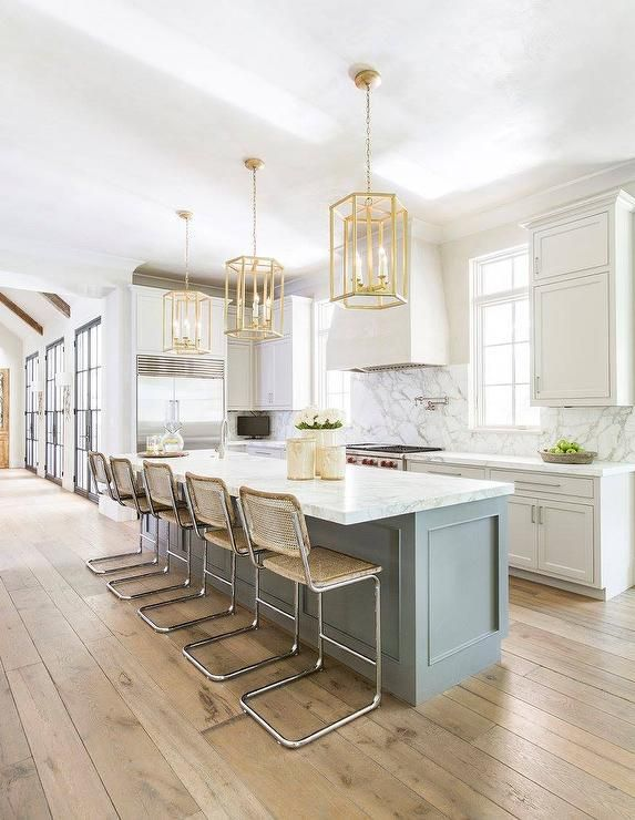 Three gold hexagon lanterns illuminate a long, gray kitchen island topped with honed white marble fitted with a prep sink lined with vintage bar stools placed atop rustic plank floors.