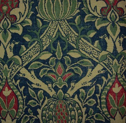 Granada Linen Fabric Printed linen in indigo, green and red depicting pomegranates within a trellis on beige background