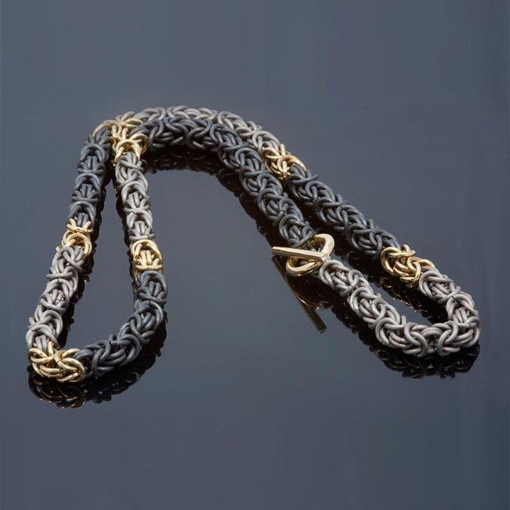 Koningscollier, gemaakt van zwart zirconium, geelgoud en titanium. De sluiting is bezet met twee diamantjes van 0,01 caraat.