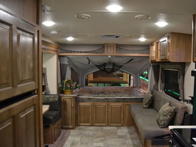 2017 Flagstaff Shamrock 233S Hybrid Travel Trailer with Slide and 3 Tents.has 3 tent ends with a Queen bed in each, a large U-shaped dinette, and a jackknife sofa. There is also an entertainment stand with a Flat screen TV and built in stereo/DVD player. The kitchen host a 3 burner stovetop with a glass cover, a double basin sink with cover, a microwave as well as a large double door refrigerator.