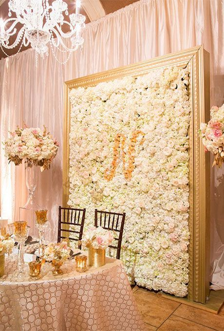 Brides.com: . An all-white flower wall with a contrasting floral monogram is a chic way to personalize your big day.