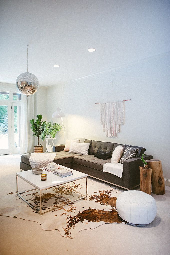 Gray sofa with woven wall hanging, modern coffee table, white pouf and cowhide rug