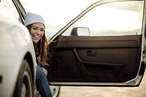 Young woman sitting in car, smiling