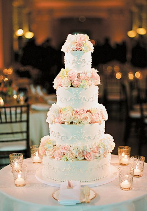 Glamorous four tier white wedding cake wrapped with blush flowers; Featured Photographer: Lisa Lefkowitz