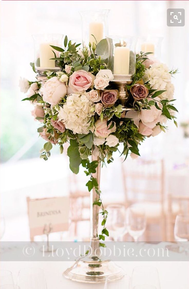 A lovely floral centre piece with fake flowers and romantic a candle.