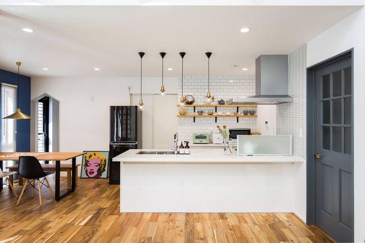 【キッチン・ダイニング】 アメリカンテイストのLDK。白をベースに、アカシアの無垢床、グレーの無垢の建具や黒を用いたインテリアをアクセントとして採用。照明や小物にまでこだわり、バランスの良い空間になりました。