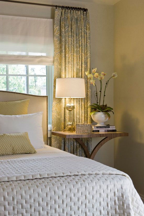 Blue-greens, cream, and hints of muted chartreuse from the draperies also make an appearance in the plush bedding and upholstered headboard. - Traditional Home ®