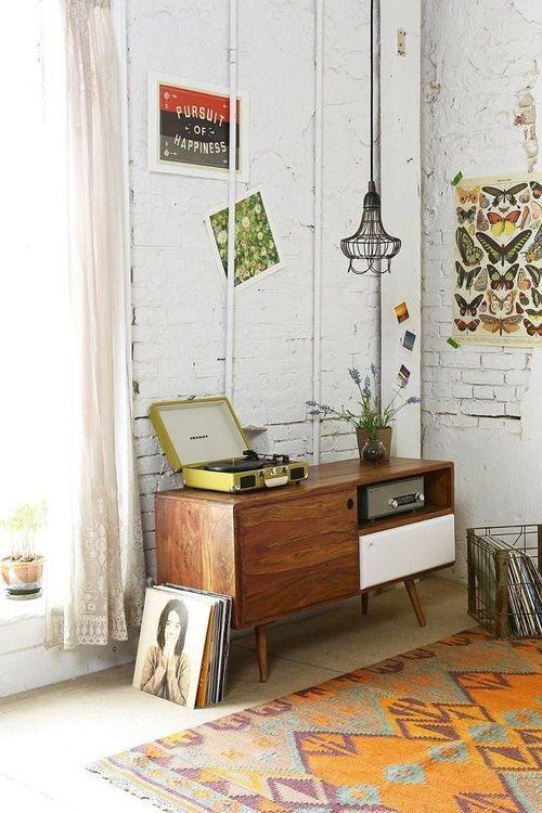 tapete étinico, abuffet vintage com toca discos e vinis, parede de tijolos a vista branca, cortina de renda
