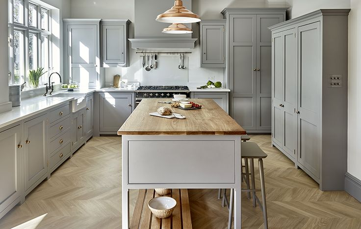 Surbiton kitchen design by Brayer with bespoke cabinets with grey finish, kitchen island with oak top, parquet flooring and copper accents.