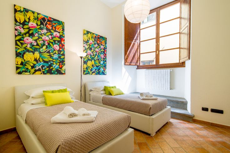 The first bedroom, bright and modern with double beds.