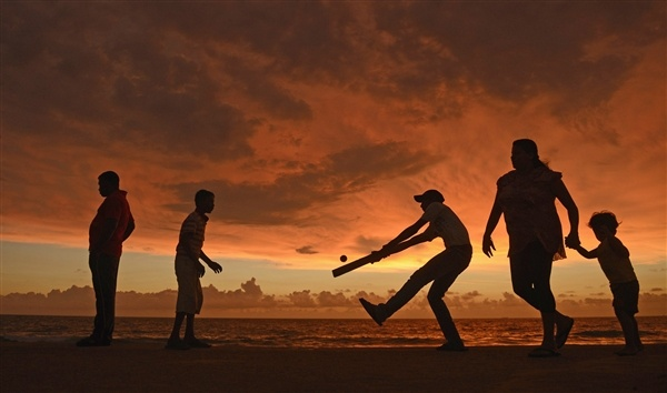 Cricket on the beach under an electric-orange sky  A boy hits a ball as people walk along the seafront in Colombo, Sri Lanka, Oct. 6, 2012.