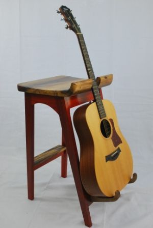 The stool frame is Padauk, and the seat, guitar supports, and foot rest are all carved from a solid piece of Oregon Myrtle wood. I wanted a stand for my guitars, AND a place to sit and play, and this...
