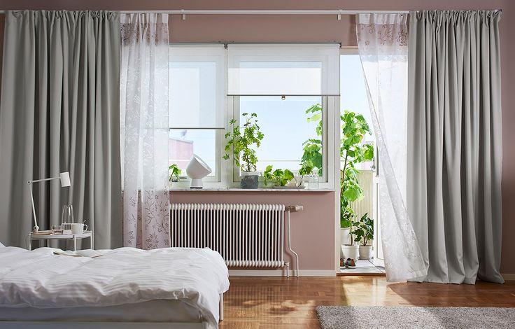 Lyst soveværelse med vinduer med hvide rullegardiner, 1 lag tynde hvide gardiner, der filtrerer dagslyset, og 1 lag tykke grå mørklægningsgardiner, der gi'r privatliv.