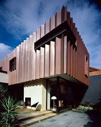 Copper-concertina clad perched over a receding glazed wall beneath, showing us how cladding can instantly renovate and update and older home.