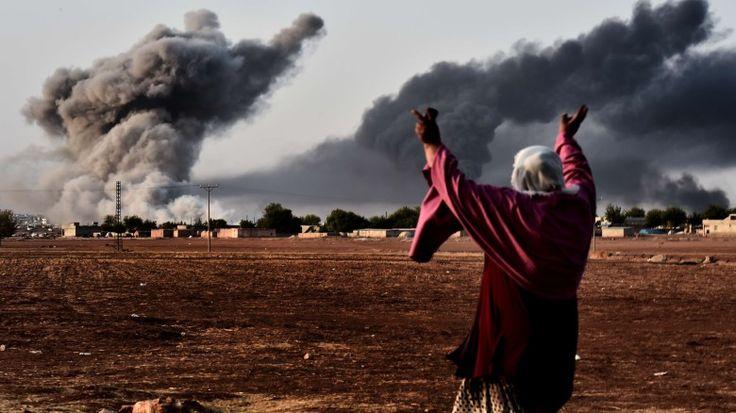Luftschlag der Koalition: Schwarzer Rauch steigt über Kobani auf, die Frau im Vordergrund auf der türkischen Seite reißt die Armee hoch. Die Angriffe könnten weit effektiver sein