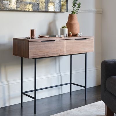 The slim profile on the Antwerp console table is covered in a warm walnut veneer and sat on equally slim, slightly recessed, rounded black powder coated metal legs.  The overall effect is elegance which is further emphasised with its complimentary horizontal handles, centrally placed on the two drawer tops which all have soft close mechanism. This console table comes fully assembled.