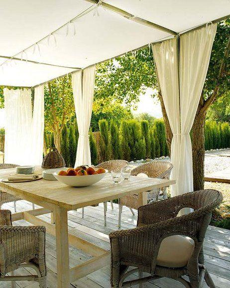 comedor de verano con pérgola de hierro y cortinas