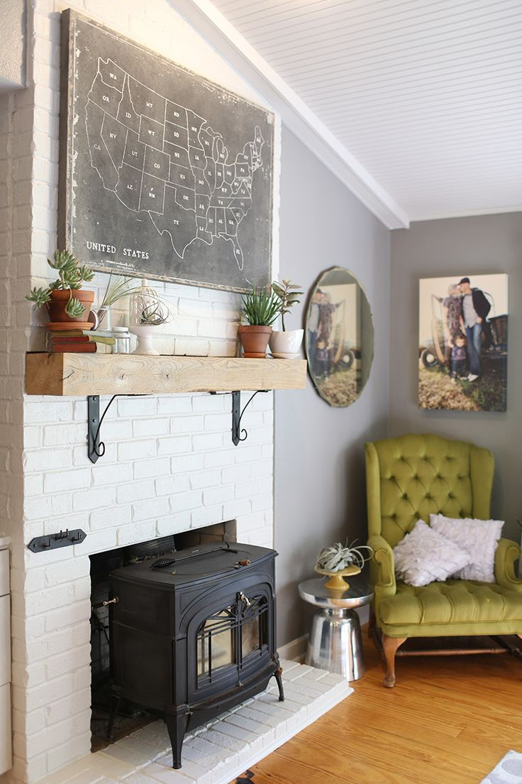wood stove inside fireplace, mantel with brackets, map
